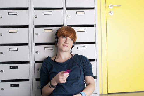 Germany, Leipzig, Young woman sitting and listening music in locker room - BABF00567
