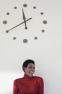 Germany, Leipzig, University student laughing with wall clock in background - BABF00513