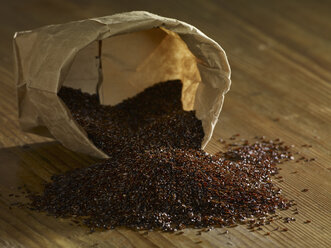 Psyllium seeds spilling on wooden surface - SRSF00193