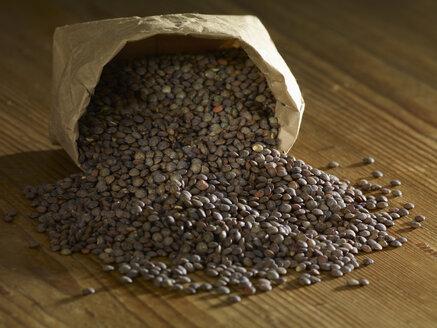 Puy lentils spilling on wooden surface - SRSF00160