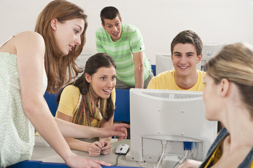 Germany, Emmering, Students using computer in computer lab, smiling - RNF00348