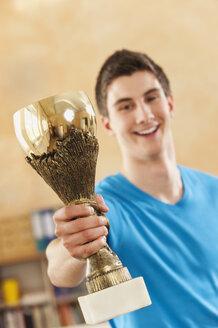 Germany, Emmering, Teenage boy holding trophy, smiling, portrait - RNF00333