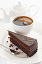 Slice of Sacher cake in plate with coffee cup and kettle in background - 13329CS-U