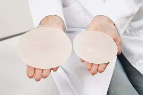 Germany, Munich, Doctor holding breast implant, close up - WESTF14809