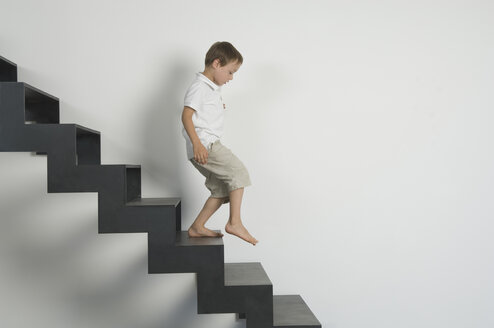 Germany, Boy (4-5 years) moving down from stairs - CRF001913