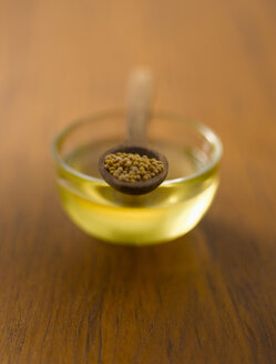 Mustard seeds in wooden spoon on bowl of oil - KSWF000565