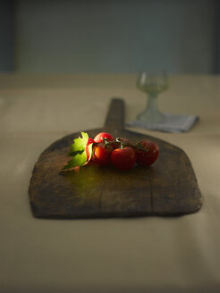 Tomatoes on wood with wine glass in background - KSWF000563