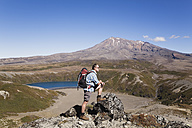 New Zealand, North Island, Man hiking at tongariro national park with mount ruapehu in background - GWF001232