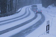 Germany, Bavaria, Schaeftlarn, View of cars moving on road covered with snow - TCF001339