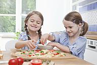 Germany, Munich, Girls (4-7) preparing food in kitchen - RBF000308
