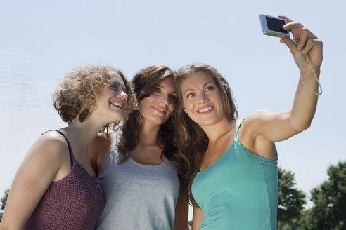 Germany, Munich, Women capturing photo, smiling - LDF000856