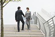 Germany, Hamburg, Business people shaking hands at stairway, smiling - WESTF015272
