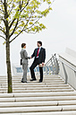 Germany, Hamburg, Business people shaking hands at stairway, smiling - WESTF015275
