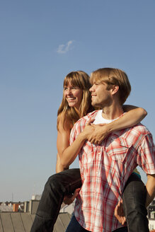 Germany, Bavaria, Munich, Young couple enjoying on rooftop - SKF000385