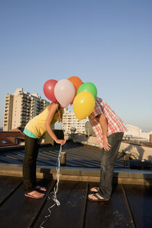 Germany, Bavaria, Munich, Young couple covered by balloons on rooftop - SKF000375