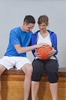 Germany, Berlin, Young woman and man looking at basketball - BAEF000104