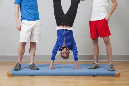 Germany, Berlin, Young woman practising handstand in school gym - BAEF000155
