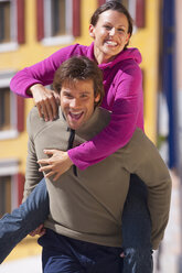 Italy, Trentino, Mature man carrying piggy back of young woman - KEF000053