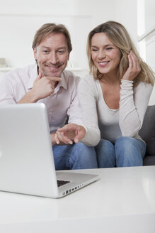Couple using laptop, smiling - LDF000893