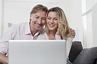 Couple using laptop, smiling - LDF000905