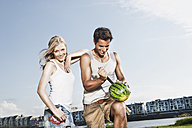Germany, Cologne, Man cutting watermelon, woman smiling - JOF000176