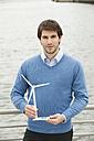 Germany, Hamburg, Businessman holding wind turbine, portrait - WESTF015448