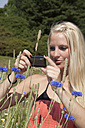 Germany, Dortmund, Young woman capturing an image with cell phone - SKF000294