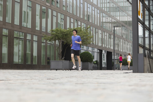 Germany, Cologne, Young man and women jogging - SKF000309