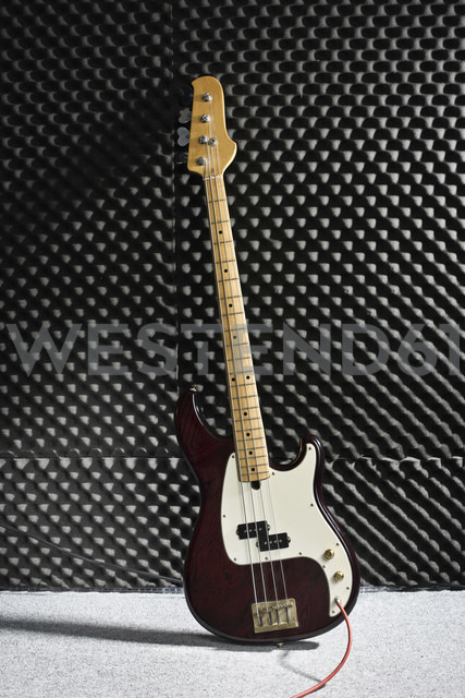 Germany, Electric bass guitar against wall, close up - MFF000439