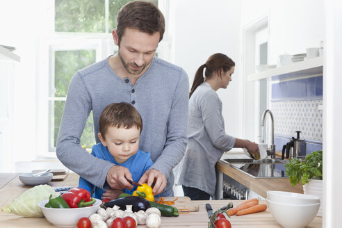 Germany, Bavaria, Munich, Father and son (2-3 Years) chopping pepper and mother in background - RBF000362