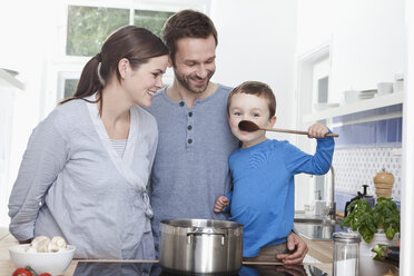 Germany, Bavaria, Munich, Family in the kitchen with boy (2-3 Years) tasting meal - RBF000379