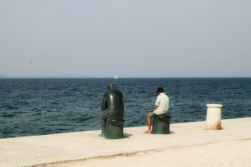 Slovakia, View of person sitting beside sculpture at seaside - HK000354