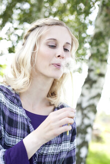 Germany, Saxony, Young woman blowing dandelion flower - MBF001129