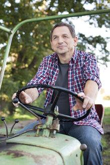 Germany, Saxony, Senior man sitting on tractor, smiling - MBF001065