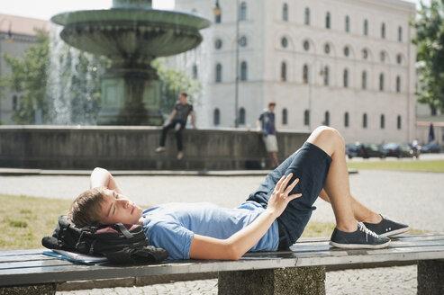 Germany, Munich, Karlsplatz, Young man resting on bench in university - RNF000403