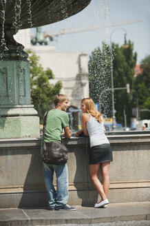 Germany, Munich, Young man and young woman at fountain in university - RNF000388