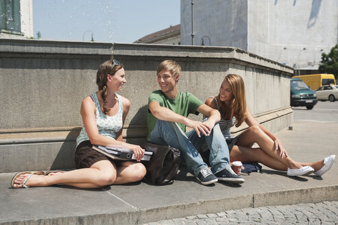 Germany, Munich, Young man and young women sitting at fountain in university - RNF000385