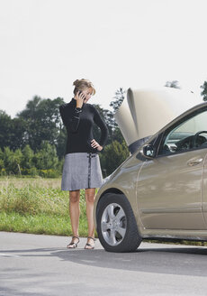 Germany, Augsburg, Young woman standng by car on road using mobile phone - WBF000030