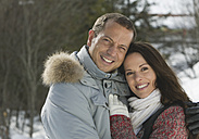 Germany, Bavaria, Couple hugging in winter, smiling, portrait - WBF000530