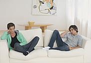 Man and boy get bored sitting on sofa - WBF000533