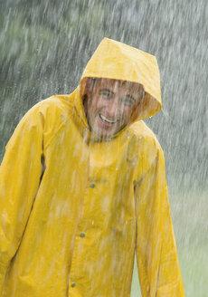 Man wearing rain coat standing in rain, portrait - WBF000782