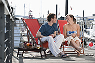Germany, Hamburg, Couple relaxing in deck chair on floating home, smiling - WESTF015595