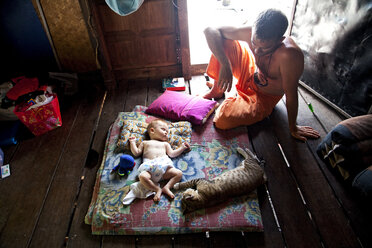 Thailand, Baby and cat sleeping with man sitting - ND000170