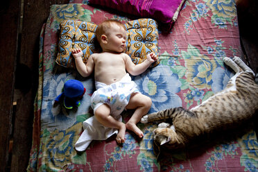 Thailand, Baby and cat sleeping on bed - NDF000154