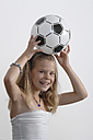 Girl (10-11 Years) with football, smiling, portrait - CRF001930