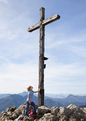 Germany, Bavaria, Boy (4-5 Years) on mountain summit looking at cross - HSIF000022