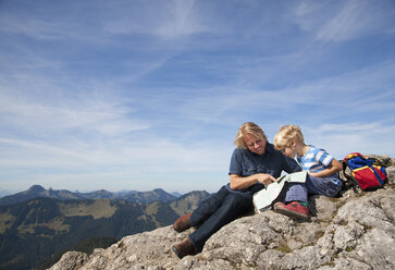 Germany, Bavaria, Father and son (4-5 Years) looking into map at mountain summit - HSIF000021