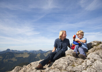 Germany, Bavaria, Father and son (4-5 Years) looking away with map on mountain summit - HSIF000019