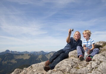 Germany, Bavaria, Father and son (4-5 Years) taking photos on mountain summit - HSIF000016