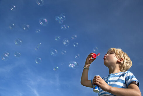 Germany, Bavaria, Boy (4-5 Years) blowing soap bubbles - HSIF000005